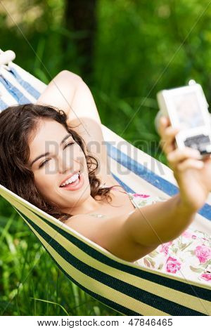 Young woman lying in a hammock in garden doing snapshot.