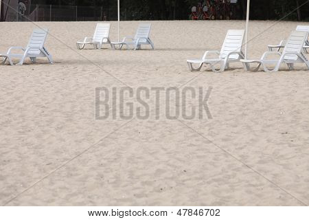 White Pool Chairs On Sand Beach