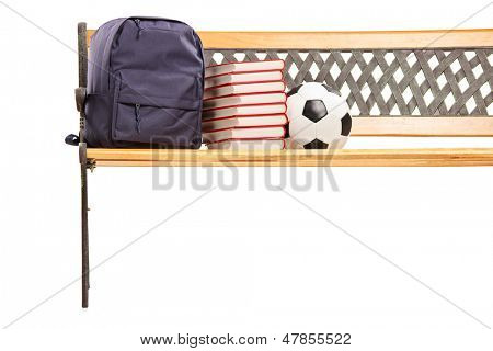 Studioaufnahme von einer Holzbank mit Büchern, Schultasche und Mannschaftssport drauf, isolated on white backgro