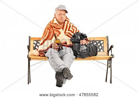 Drunk homeless mature man sitting on a bench and holding a bottle, isolated on white background
