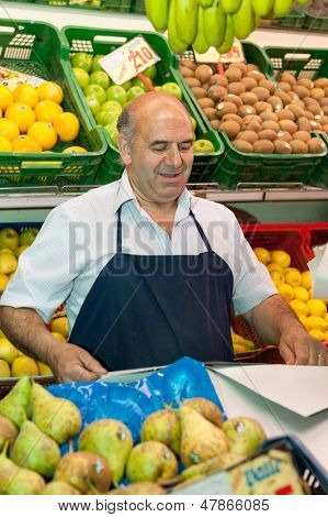 Greengrocer at the market stall