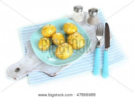 Boiled potatoes on platen on wooden board on napkin isolated on white