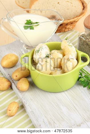 Tender young potatoes with sour cream and herbs in pan on wooden board on table close-up