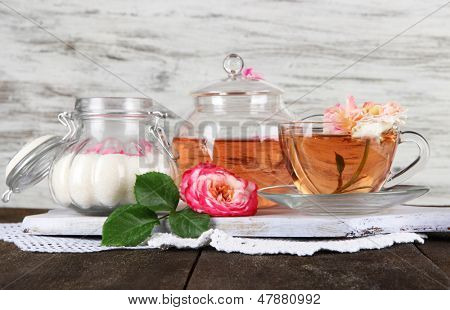 Kettle and cup of tea from tea rose on board on napkin on wooden table on wooden background