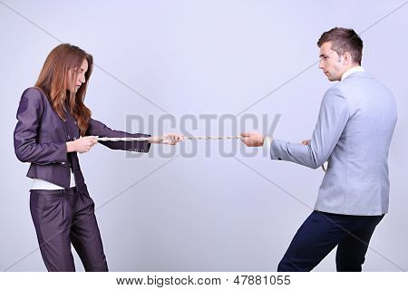 Business people stretching rope on grey background