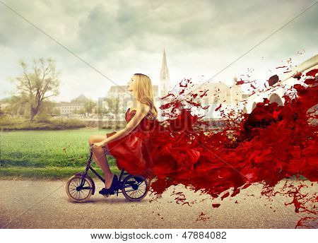 beautiful woman cycling with elegant red dress