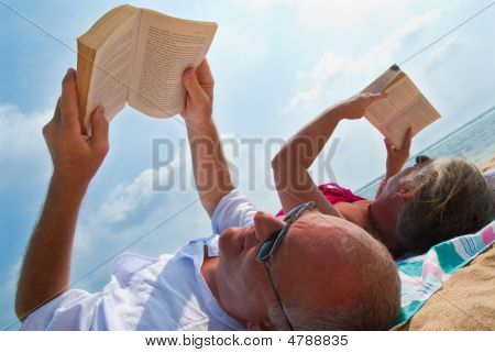 Mature Couple Reading On Beach