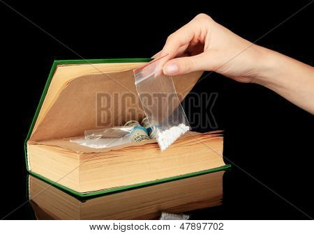Hand holding narcotics near book-hiding place isolated on black