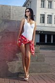 stock photo of leggy  - leggy beautiful lady standing on sidewalk of city - JPG