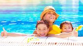 Happy family have fun in the pool, relaxation in aqua park, mother with two cute kids swimming in co