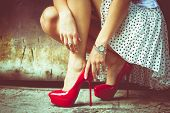 stock photo of squatting  - woman legs in red high heel shoes and short skirt outdoor shot against old metal door - JPG