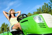 foto of grass-cutter  - Female gardener relaxing and resting after lawn mowing on summer - JPG