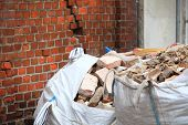 picture of dump  - Full construction waste debris bags garbage bricks and material from demolished house - JPG