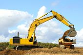 stock photo of track-hoe  - A large track hoe exchavator loads a large articulating dump truck at a new road project in Oregon - JPG