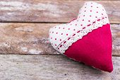 red textile heart on wooden background