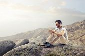 image of disgusting  - young disgusted man sitting on the rocks looking the tablet - JPG