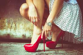 pic of short legs  - woman legs in red high heel shoes and short skirt outdoor shot against old metal door - JPG