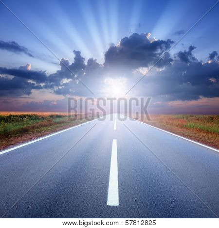 Driving On Asphalt Road Towards The Sunbeams