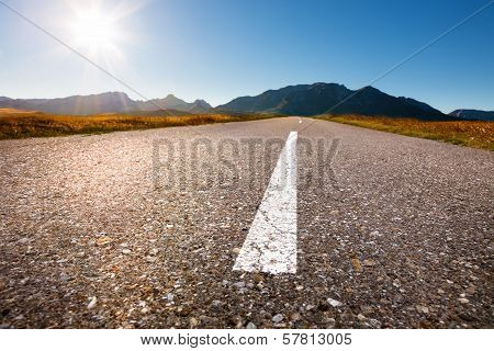 Driving On Asphalt Road Towards The Sun