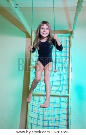 Child At Her Home Sports Gym Swinging