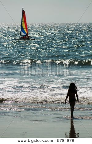 The Outline of a child on a beach admiring a sailboat