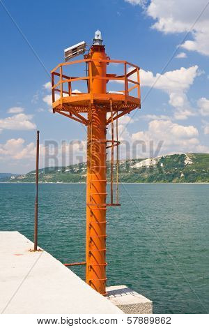 Small Red Lighthouse On Harbor Entrance Of Balchik, Against Great Blue Sky