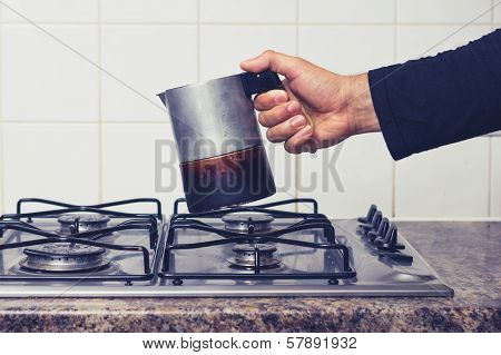 Man's Hand Placing Espresso Maker On Stove