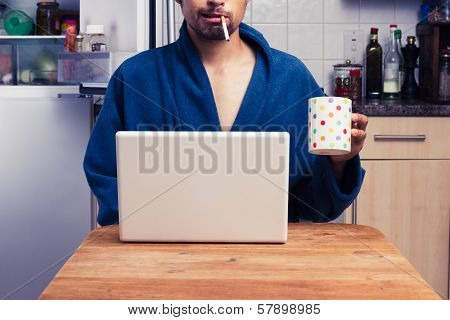 Man In Robe Working From Home And Smoking