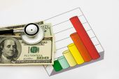 foto of health-care  - A one hundred dollar bill and stethoscope on a graph that is on a white background increased healthcare costs - JPG