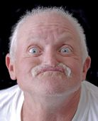 stock photo of asymmetrical  - Image of a funny old man making a face - JPG