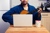foto of cross-dressing  - Man Teaching Himself To Play Guitar At Home - JPG