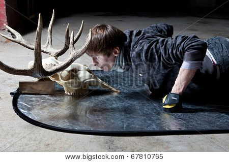 Young man lying down looking at the deer skull in a dark basement