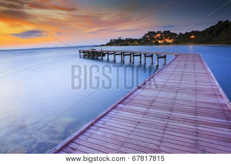 Wood Bridge Piers With Nobody And Smoothy Sea Water Against Beautiful Sun Rising Sky