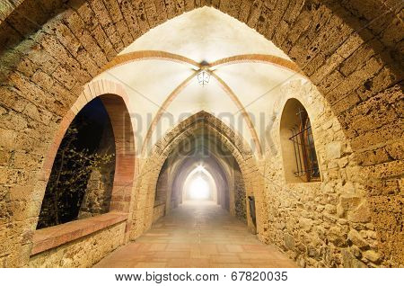 Fantasy corridor. Ancient Monastery corridor with light at the end.