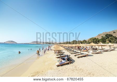 MYKONOS GREECE - AGOUST 23: Wide sand beach with tourists umbrellas and beds on Agoust 23 2013.
