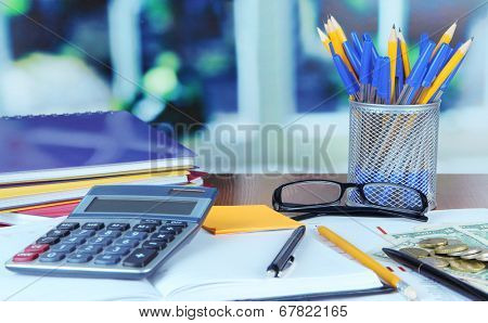 Office supplies with documents and money on table on bright background