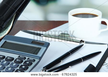 Office supplies with wallet and cup of coffee close up