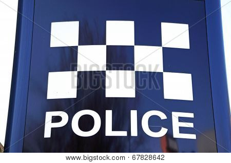Police sign with chequered design.