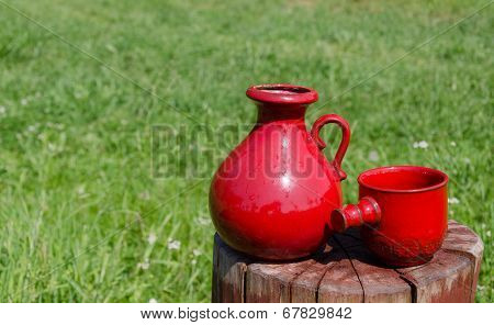 Ceramic Red Water Jug And Cup On Stump On Nature