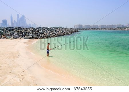 DUBAI, UAE - 1 APRIL 2014: Unidentified man fishing on the Jumeirah Beach in Dubai, UAE. Jumeirah Beach is a white sand beach that is located and named after the Jumeirah district of Dubai.