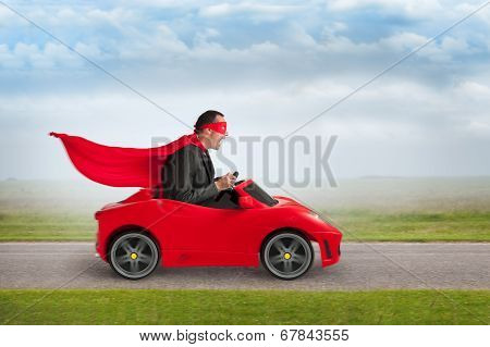 Superhero Man Driving A Toy Racing Car