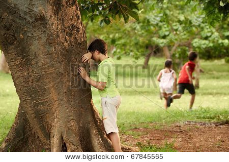 Male And Female Children Playing Hide And Seek