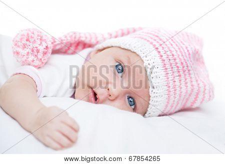newborn baby seven weeks age in hat on white background