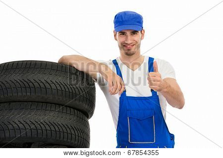 Young mechanic with tyre showing ok sign hand