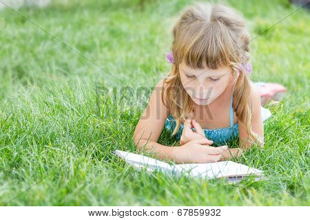young child girl reading book outdoors on natural background