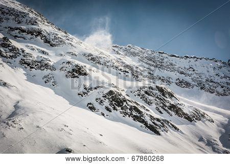 Mountain Ridge With Wind Blowing Off Some Snow