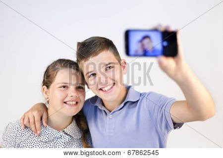 A boy and a girl taking a self portrait with smart phone against gray background