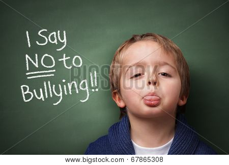 Little boy standing up for himself and saying NO to bullying by blowing a raspberry at the bully in front of a blackboard at school