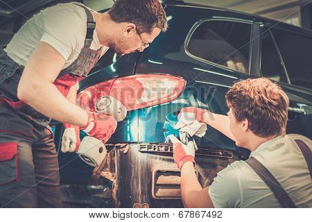 Two workers with colour samples choosing correct tone in a car body workshop