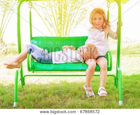 Two adorable child spending leisure time on swing, having fun in summer camp, active holidays, happiness and friendship  concept